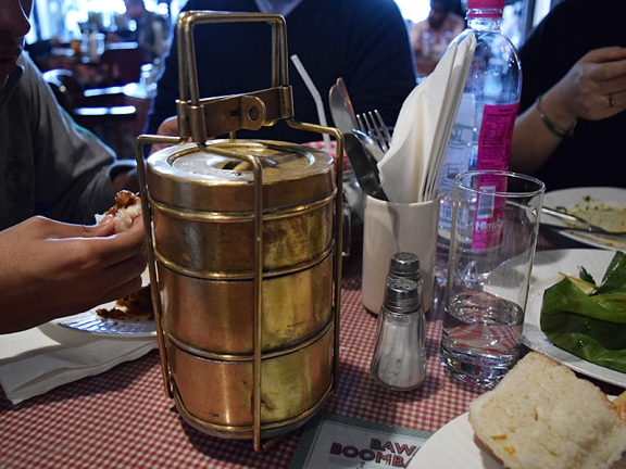 The dhansak is served, unnecessarily, in an old-school tiffin carrier.