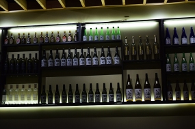 As you enter you will see that the room is small, that the kitchen is visible at one end and that one wall is lined with sake bottles.