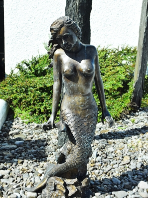 This statue of a mermaid who is obviously feeling the cold weather is off to the side.