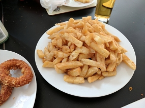 Another huge mound of chips; onion rings barely visible alongside.