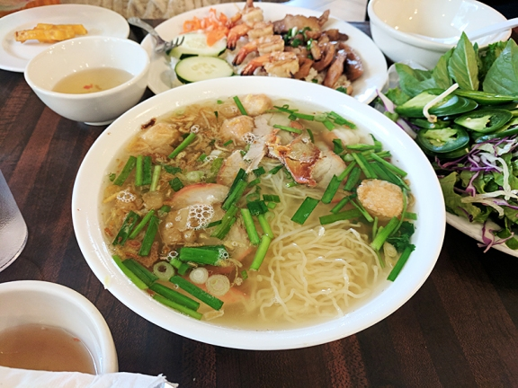 Rice and yellow egg noodles together in pork broth with seafood and pork.