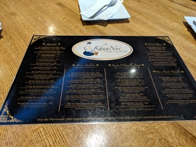 The glossy material and gold lettering on a black background make the menu quite challenging to read under the bright lights.
