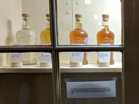 Bottles from their core range alongside a bottle of new make, showing the effect of cask type and age on colour.