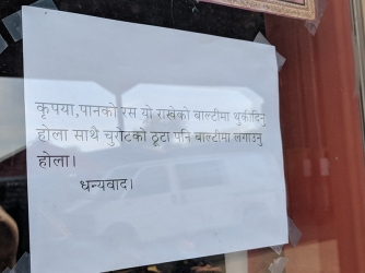I don't speak Nepali but it uses the Nagari script that Hindi uses and the languages are close enough that I can tell you that this sign asks people not to spit around the store.