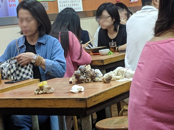 It's common at restaurants like this in Hong Kong for people to just dump/spit bones onto the table as they eat.